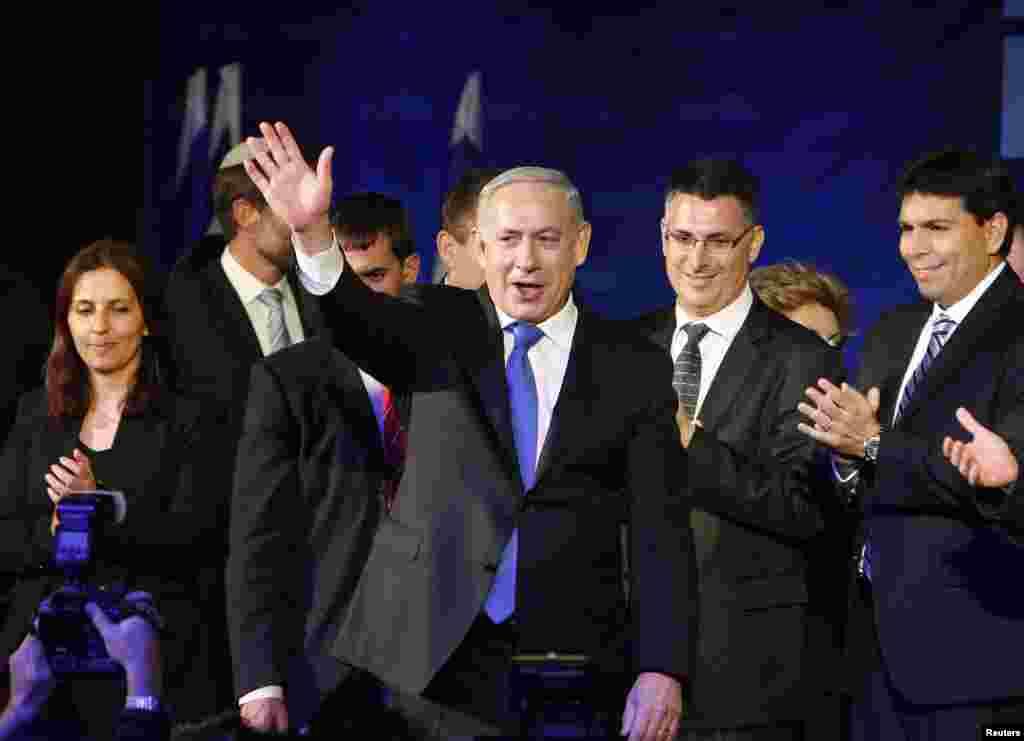 Perdana Menteri Israel Benjamin Netanyahu melambaikan tangannya pada para pendukung bersama anggota partai Likud-Yisrael Beitenu di Tel Aviv (23/1). Netanyahu menang tipis dalam pemilihan umum Selasa, meski kursi parlemen partainya banyak direbut oleh oposisi dari kelompok tengah-kiri. (Reuters/Nir Elias)