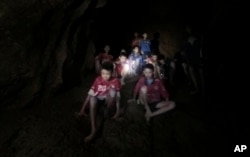 This July 2, 2018, photo released by Tham Luang Rescue Operation Center, shows the boys and their soccer coach as they were found in a partially flooded cave, in Mae Sai, Chiang Rai, Thailand.