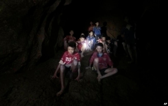 This Monday, July 2, 2018, photo released by Tham Luang Rescue Operation Center, shows the boys and their soccer coach as they were found in a partially flooded cave, in Mae Sai, Chiang Rai, Thailand.