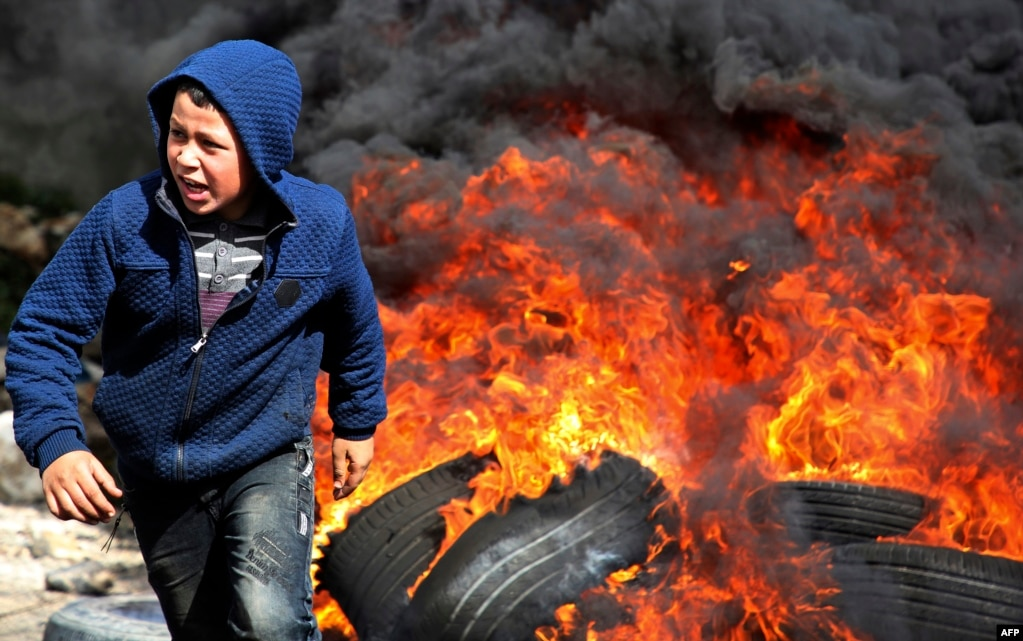 A Palestinian boy runs away from flaming tires during a weekly demonstration against the seizing of Palestinian land by Israel, in the village of Kfar Qaddum, near Nablus in the occupied West Bank.