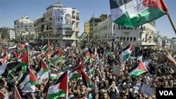Warga Palestina melambaikan bendera dan menyerukan slogan dalam demonstrasi rekonsiliasi Hamas dan Fatah di Tepi Barat.