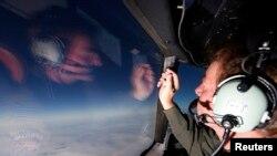 在一架在印度洋南部搜索失踪马航班机的新西兰皇家空军P3-K猎户座飞机上,空军少校布赖特•麦肯齐借着机窗记录其它飞机的搜寻结果。(资料照)
