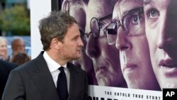 "FILE - Jason Clarke looks at a movie poster as he arrives at the premiere of ""Chappaquiddick"" at the Samuel Goldwyn Theater, March 28, 2018, in Beverly Hills, California."