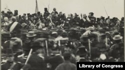 National Cemetery in Gettysburg, Penn., where President Abraham Lincoln gave his now famous speech, the Gettysburg Address. Lincoln is visible facing the crowd, not wearing a hat, about an inch below the third flag from the left. Josephine Cobb first found Lincoln's face while working with a glass plate negative at the National Archives in 1952. (Library of Congress)