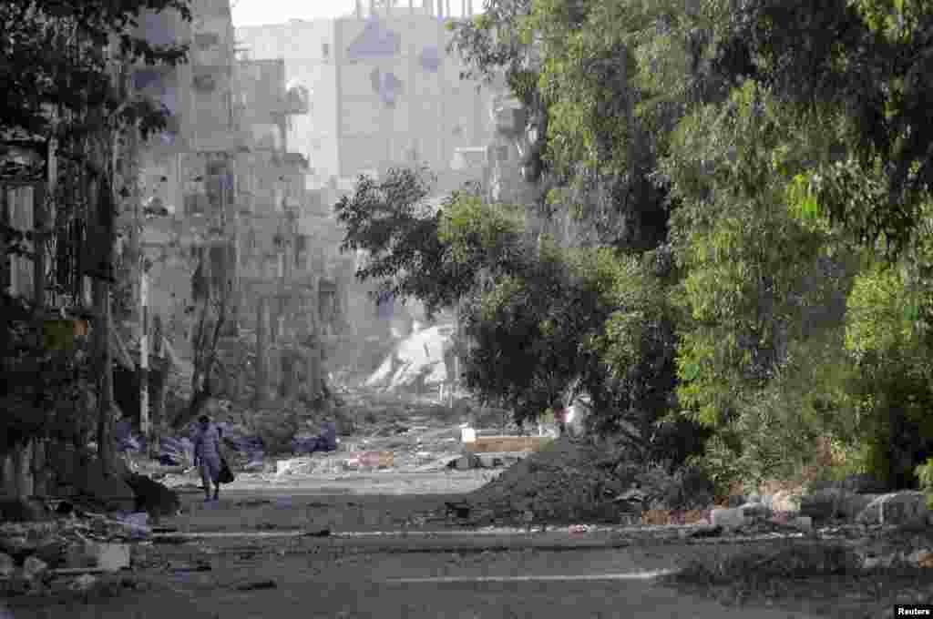 A man walks along a street filled with debris in Deir al-Zor, June 17, 2013.