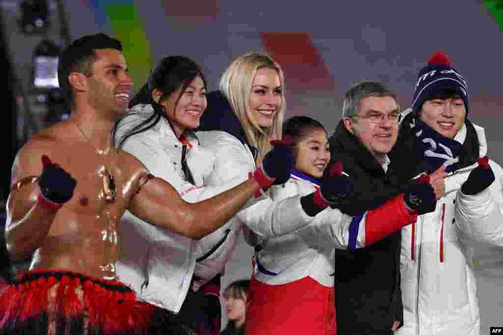 平昌冬奥会闭幕式上,国际奥委会主席巴赫邀请几位运动员上台。左起:汤加旗手陶法托富阿,中国选手、单板滑雪银牌得主刘佳宇,美国滑雪运动员、铜牌得主林赛·沃恩,朝鲜花样滑冰选手廉太玉,国际奥委会主席巴赫,韩国冰橇运动员、金牌得主尹诚彬。(2018年2月25日)