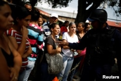 Relatives of inmates talk to a police officer as they wait for information after a riot and a fire in the cells of the General Command of the Carabobo Police in Valencia, Venezuela, March 29, 2018.