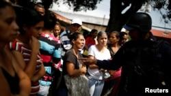 Des proches de détenus discutent avec un policier en attendant des informations après une émeute et un incendie dans les cellules du quartier général de la police de Carabobo à Valence, au Venezuela, le 29 mars 2018.