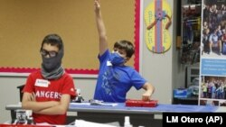 In this July 14, 2020, file photo, amid concerns of the spread of COVID-19, Aiden Trabucco, right, wears a mask as he raises his hand to answer a question behind Anthony Gonzales during a summer STEM camp at Wylie High School in Wylie, Texas.
