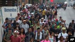 Imigran Peyi Ondiras ki pran apye wout k ap mennen yo Ozetazini an pasan pa Gwatemala avèk Meksik. (Foto: 17 oktòb 2018).