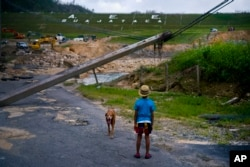FILE - In this Oct. 17, 2017 file photo, a boy accompanied by his dog watches the repairs of Guajataca Dam, which cracked during the passage of Hurricane Maria, in Quebradillas, Puerto Rico.