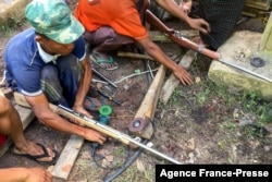 FILE - Members of the People's Defense Force (PDF) make handmade guns to be used in their fight against security forces, near Demoso, Kayah state, Myanmar, as the country remains in turmoil after the February military coup.