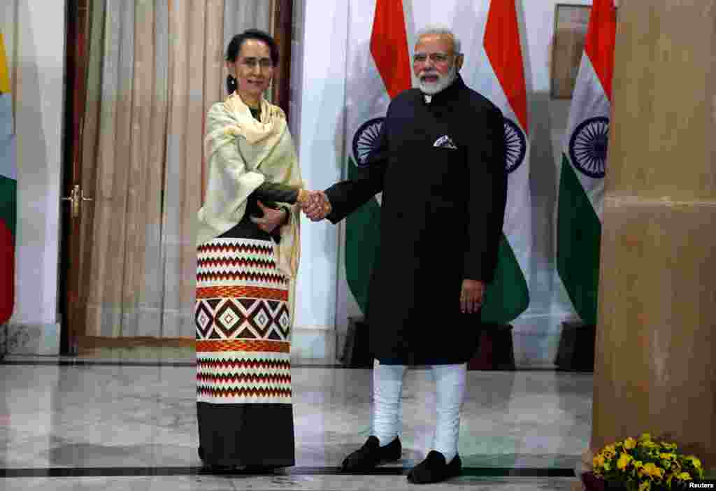 Myanmar's State Counsellor Aung San Suu Kyi shakes hands with India's Prime Minister Narendra Modi during a photo opportunity ahead of their meeting at Hyderabad House in New Delhi, India, January 24, 2018. REUTERS/Cathal McNaughton - RC1F3681AF70