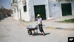 一个利比亚男孩在的黎波里用独轮车运水