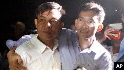 Hai nhà báo Campuchia, Uon Chhin, trái, và Yeang Socheamet, phải, ôm vai nhau bước ra khỏi nhà tù Prey Sar ở ngoại ô thủ đô Phnom Penh, Campuchia, ngày 21/8/2018. Cả hai từng cộng tác với RFA-Khmer. (AP Photo/Heng Sinith)