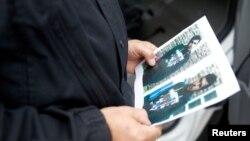 Policajac drži fotografiju osumnjičenog Sirijca Džabera Albakra
