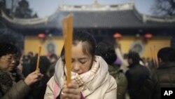 Seorang perempuan berdoa di kuil Longhua pada hari pertama Tahun Baru China di Shanghai, Februari 2013. (Foto: Dok)
