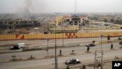 Xe cộ bị đốt và các tòa nhà bị hư hại ở Fallujah, 65 km về phía tây của Baghdad, Iraq, 3/1/2014