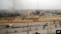 伊拉克西部城市費盧傑的大街上空蕩蕩只有被燒的汽車和破壞的建築物。