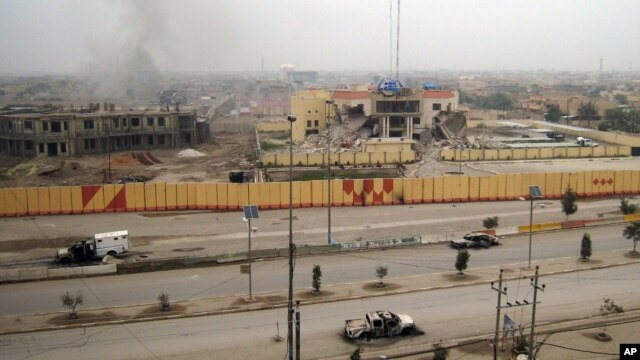 An empty street shows burned vehicles and damaged buildings in Fallujah, 65 kilometers west of Baghdad, Iraq, Jan. 3, 2014.