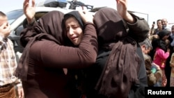 Members of the minority Yazidi sect who were newly released hug each other on the outskirts of Kirkuk April 8, 2015. More than 200 elderly and infirm Yazidis were freed on Wednesday by Islamic State militants who had been holding them captive since overru