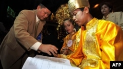 FILE - An Indonesian couple takes part in a mass interfaith wedding ceremony sponsored by an organizer and the Jakarta government in Jakarta on July 19, 2011.