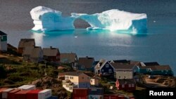 FILE - An iceberg floats near a harbor in the town of Kulusuk, east Greenland August 1, 2009.