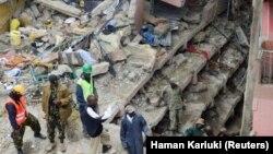 Petugas penyelamat mencari penghuni yang ditakutkan terperangkap dalam puing-puing bangunan yang ambruk akibat hujan deras di Nairobi, Kenya (30/4). (Reuters/Harman Kariuki)