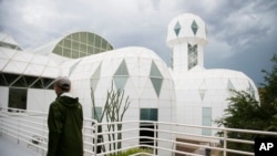 In this July 31, 2015 photo, a tourist walks to the main entrance of the Biosphere 2 facility while on a walking tour in Oracle, Ariz. (AP Photo/Ross D. Franklin)