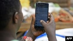 Une femme passe en revue son compte WhatsApp sur son téléphone, à Kampala, le 5 juillet 2018.