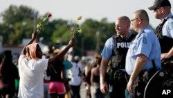 Policías observan una protesta en Ferguson, donde el Concejo de la ciudad se reune este martes por primera vez desde la muerte de Michael Brown.