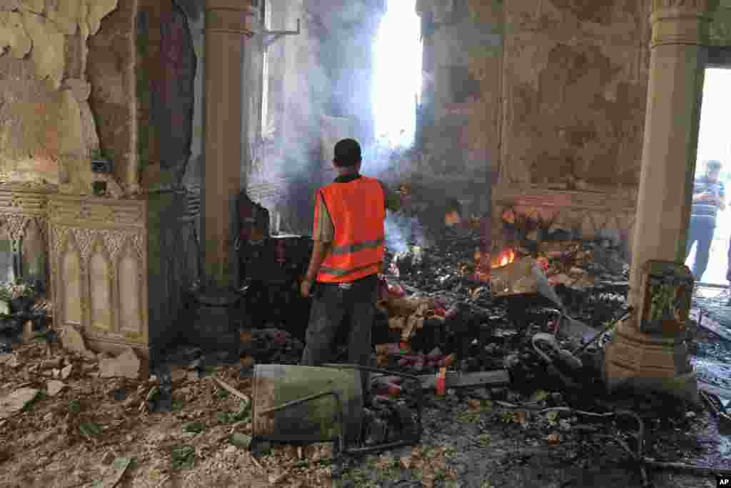 2013 年 8 月 15 日,开罗纳赛尔城,一位埃及人拍摄被烧毁的清真寺的废墟。这座清真寺位于被安全部队清理的示威者营地的中心