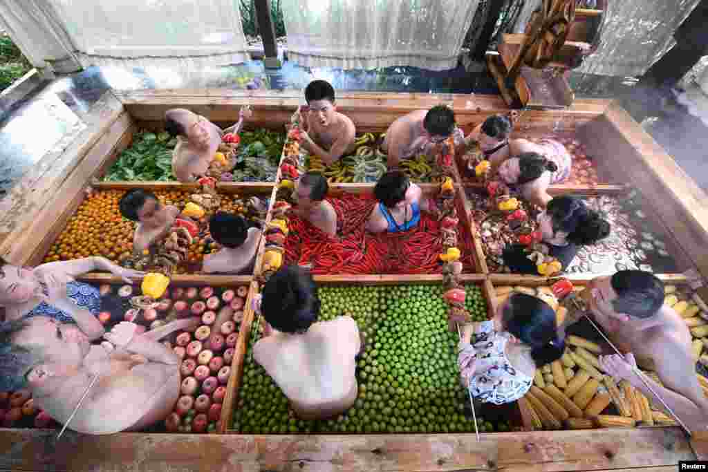 People enjoy a barbecue as they bath in a hotpot-shaped hot spring filled with fruits and vegetables, at hotel in Hangzhou, Zhejiang province, China.