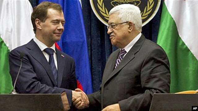Palestinian President Mahmoud Abbas, right, and Russian President Dmitry Medvedev, left, shake hands at the end of a press conference in the West Bank town of Jericho, 18 Jan 2011