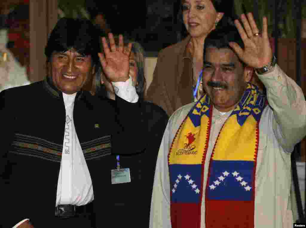 Bolivia's President Evo Morales and his Venezuelan counterpart Nicolas Maduro wave during a meeting in Cochabamba, July 4, 2013.