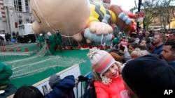 7岁的艾米莉.布朗与父亲在纽约观看参加梅西圣诞节大游行的大气球被充气吹起。(2017年11月23日)
