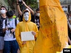 化名V的年青人穿上梁凌杰死前的黄色雨衣,象征与梁凌杰同样为民主自由站出来抗争。 (美国之音/汤惠芸)
