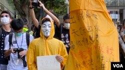 化名V的年青人穿上樑凌傑死前的黃色雨衣,象徵與梁凌傑同樣為民主自由站出來抗爭。 (美國之音湯惠芸)