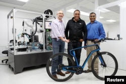 (L-R) Arevo Labs CEO Jim Miller, CTO Wiener Mondesir, and Chairman and Co-Founder Hemant Bheda stand for a photo with the company's 3-D-printed carbon fiber commuter bike in Santa Clara, California, May 10, 2018.
