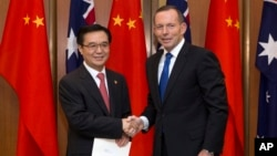 PM Australia Tony Abbott (kanan) berjabat tangan dengan Menteri Perdagangan China Gao Hucheng usai penandatanganan perjanjian perdagangan bebas kedua negara di Canberra, Rabu (17/6).