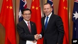 가오후청 중국 무역장관(왼쪽)과 토니 에벗 호주 총리가 17일 호주 캔버라에서 열린 자유무역협정 서명식에 악수하고 있다.