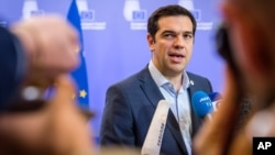 Greek Prime Minister Alexis Tsipras speaks with the media after a meeting of eurozone heads of state at the EU Council building in Brussels, July 13, 2015.