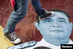 Seorang pengunjuk rasa menginjak foto Perdana Menteri Thailand Prayuth Chan-ocha dalam unjuk rasa di luar gedung parlemen, di Bangkok, Thailand, 20 Februari 2021. (Foto: Reuters/Athit Perawongmetha)