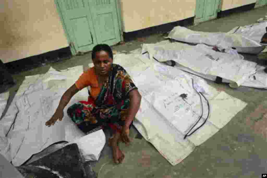 10일 방글라데시 의류공장 사고 희생자들의 시신이 주변 학교 공터에 임시로 배치되어 있다. 시신들 사이에서 지인을 시신을 찾는 다카 시민.