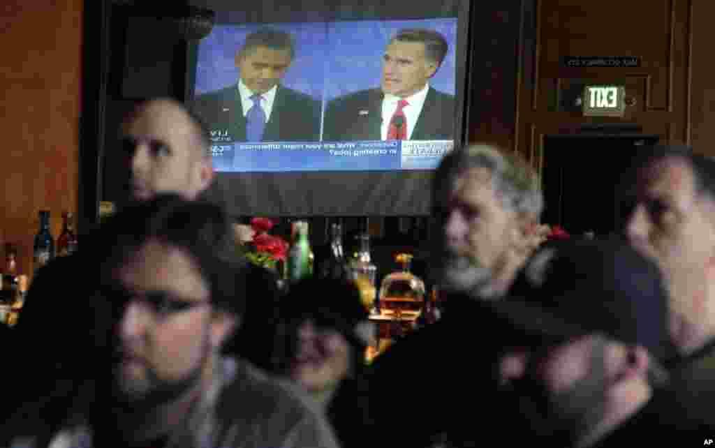 Los clientes del Havana Social Club, de Seattle, vieron el debate en un televisor, que se ve reflejado en un espejo del bar.