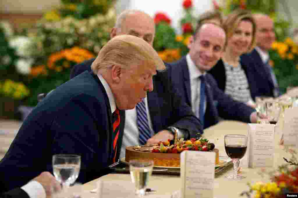 U.S. President Donald Trump blows out the candle on his birthday cake as he attends a lunch with Singapore's Prime Minister Lee Hsien Loong at the Istana in Singapore.