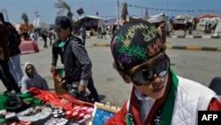 Một thanh niên bán mũ, cờ, và các quà lưu niệm khác với màu cờ của phe đối lập ở Benghazi, Libya, 15/4/2011