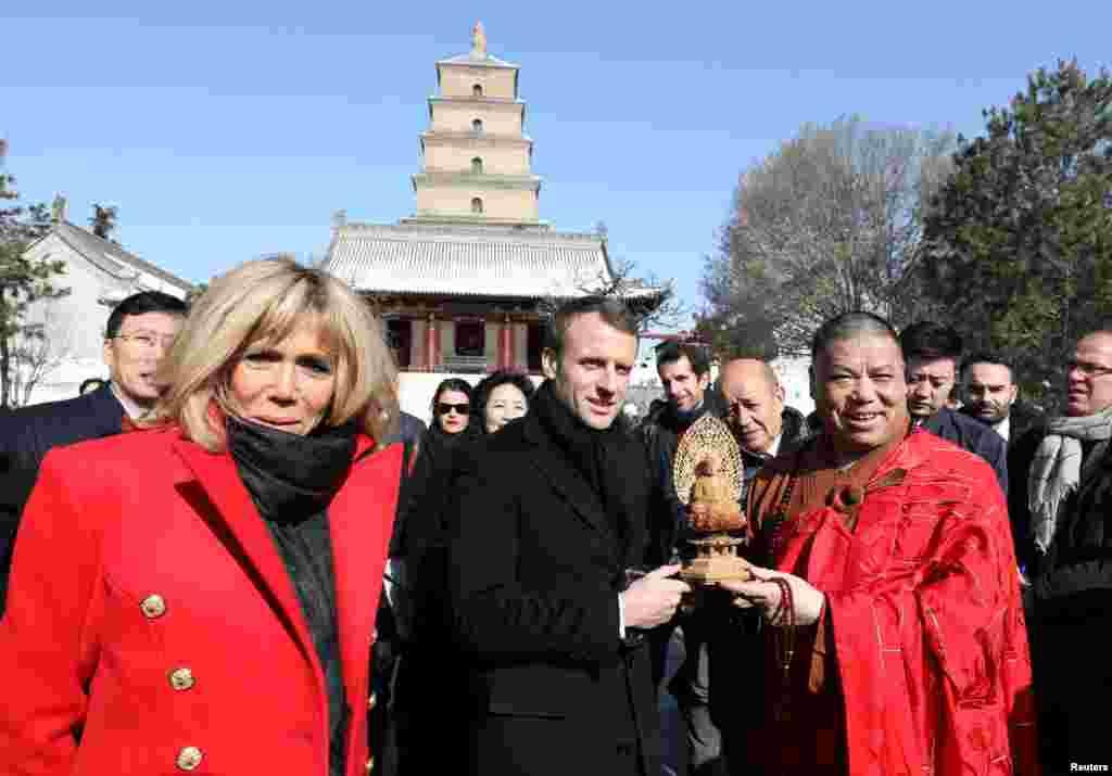 法国总统马克龙和夫人布丽吉特·马克龙(Brigitte Macron)在中国陕西省西安市参观著名的大雁塔,接受礼品(2018年1月8日)。
