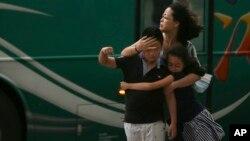 Một người mẹ giữ chặt các con giữa luồng gió của bão Soudelor ở Đài Bắc, Đài Loan, hôm 7/8/2015.