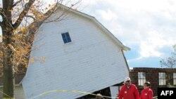 Hai nhân viên Hội Chữ thập đỏ đi ngang một nhà kho bị hất tung do lốc xoáy ở bang Wisconsin, 26/10/2010